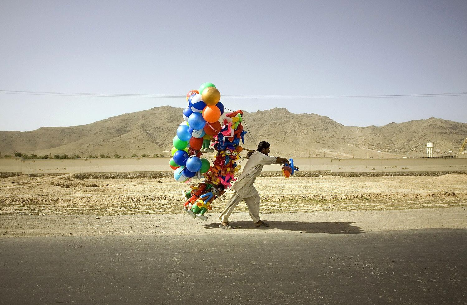 An Afghan man carries balloons alongside a road in the outskirts of Kabul. http://t.co/fJue53hqn3
