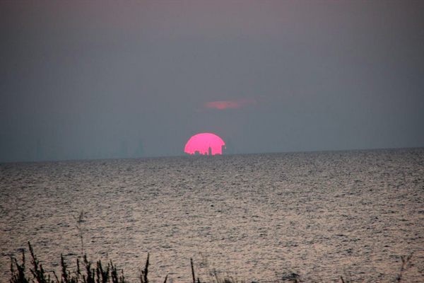 Sunset over Lake Michigan August 7th. The silhouette of Chicago inside the sun. http://t.co/dUC3hiotLZ