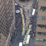 Aerial view of #FloodWallStreets MASSIVE banner & sit-in on Broadway. Crowd surrounds the Wall St Bull. http://t.co/7IuOsu2k5G
