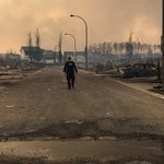 A Mountie surveys the damage on a street in Fort McMurray. #ymmfire https://t.co/6UGIfrr4SD
